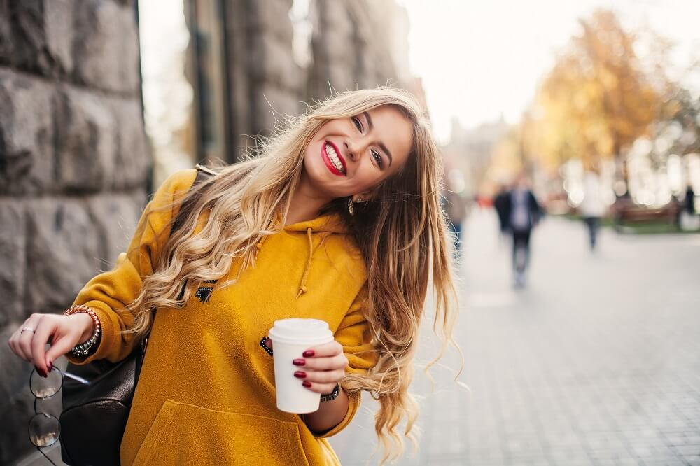 girl smiling in yellow hoodie