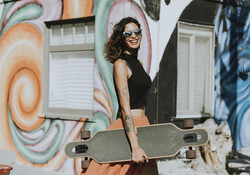 Glad tjej med vita tänder och skateboard